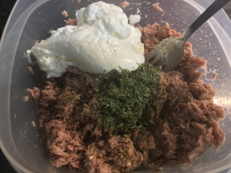 A clean plastic bowl with tuna, pickle juice, dried dill weed, salt, pepper, and mayo inside.