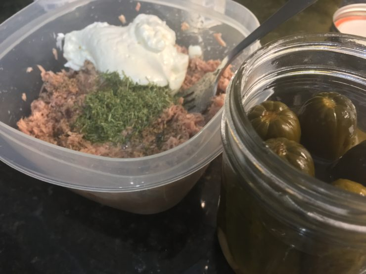 A clear plastic bowl with drained tuna, mayo, salt, pepper, dill weed, and pickle juice in the bowl with a jar of homemade pickles sitting beside the bowl.