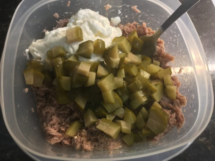 A clean plastic bowl with tuna, pickle juice, dried dill weed, salt, pepper, mayo, and diced dill pickles inside.