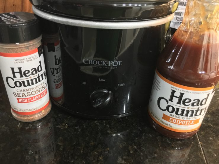 A black, two quart slow cooker with Head Country High Plains Heat seasoning and a bottle of Head Country Chipotle BBQ sitting on either side of the slow cooker.