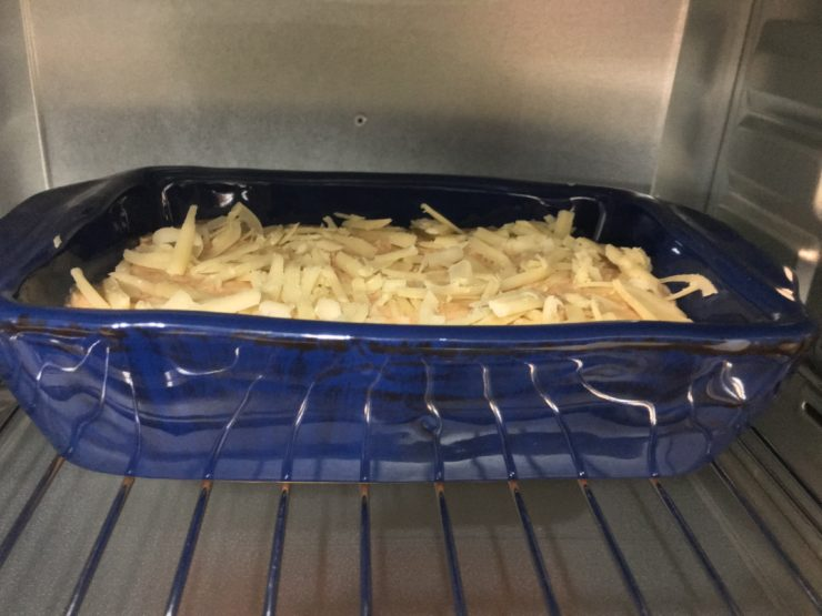A small, blue, casserole dish with BBQ Ranch Chicken dip in the dish, topped with shredded white cheddar cheese and placed in the oven.
