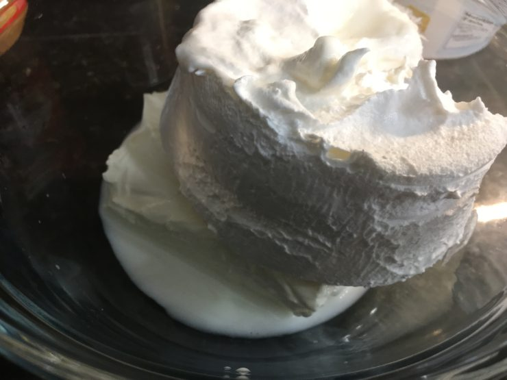 A clear, glass mixing bowl with cream cheese, milk, and cool whip in the bowl.