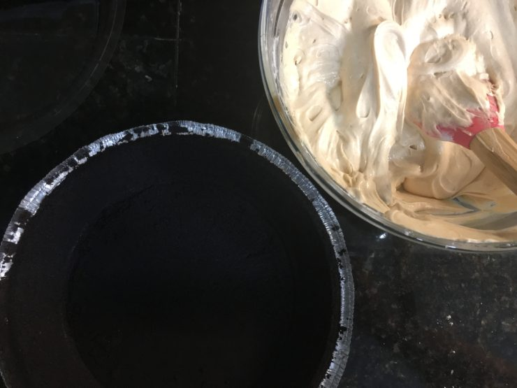 A glass bowl with Easy Peanut Butter Pie Filling inside and an empty, Oreo crust.