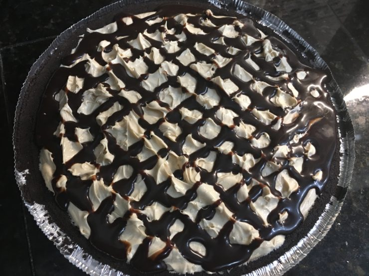 An Oreo pie crust with Easy Peanut Butter Pie in the crust. Hershey's chocolate syrup has been drizzled over the top of the Peanut Butter Pie