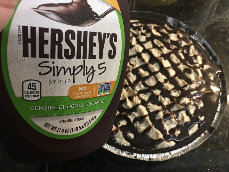 An Oreo pie crust with Easy Peanut Butter Pie in the crust. Hershey's chocolate syrup has been drizzled over the top of the Peanut Butter Pie and a hand is holding the bottle of Hershey's Simply 5 Chocolate syrup beside the peanut butter pie.