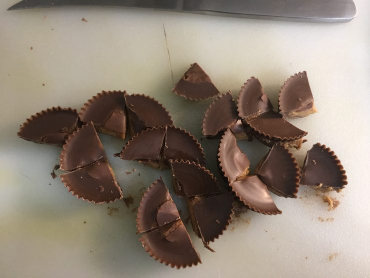 A white cutting board with chopped Reese's Peanut Butter Cups on it.