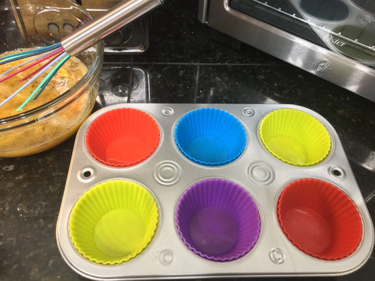 A glass bowl with whisked eggs and Head Country Seasoning in the eggs. A multi colored whisk is in the bowl and a half dozen, silver, muffin tin is sitting beside the bowl with multi colored silicone muffin liners in the tin.