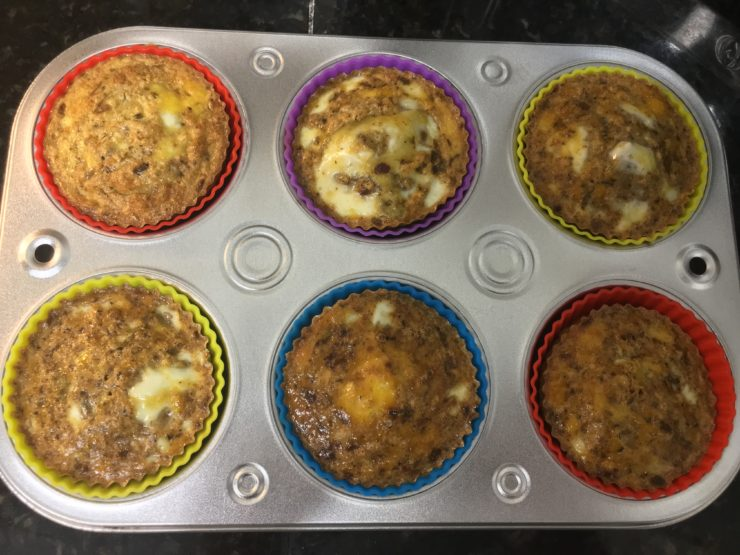A silver, half dozen muffin pan filled with multi colored silicone muffin liners and the cooked egg and Head Country Seasoning mixture.