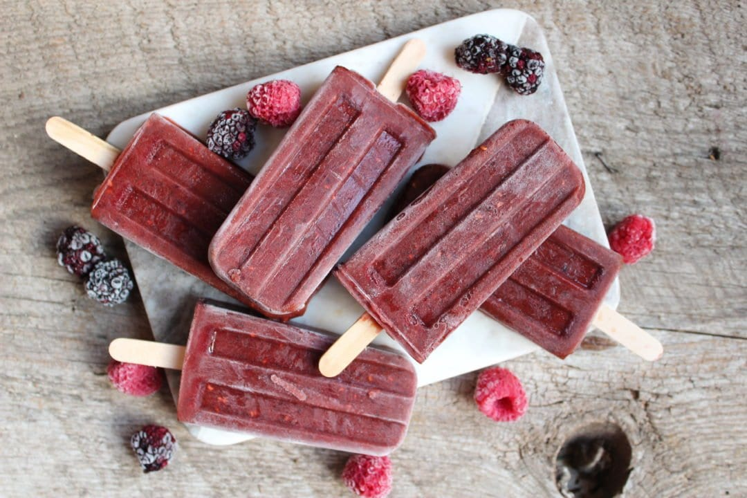 No Sugar Added popsicles on a marble cheese board with raspberries and blackberries scattered around the popsicles. Everything sits on a wood backdrop.