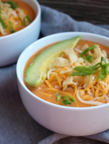 Two white soup bowls with Slow Cooker Enchilada Soup in them sitting on a wood backdrop with a blue towel under the bowls. The soup is topped with one slice of avocado, shredded cheese, chopped green onion, and wonton strips.