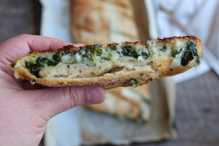 A close up photo of a slice of the Easy Spinach and Cheese Calzone with A parchment paper - lined baking sheet with the Spinach and Cheese Calzone sits in the center of a wood backdrop with a silver knife beside the pan on a white and gray striped towel in the background.