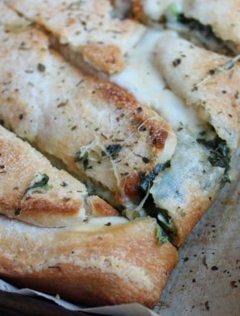 A parchment paper - lined baking sheet with the Spinach and Cheese Calzone sits in the center of a wood backdrop.