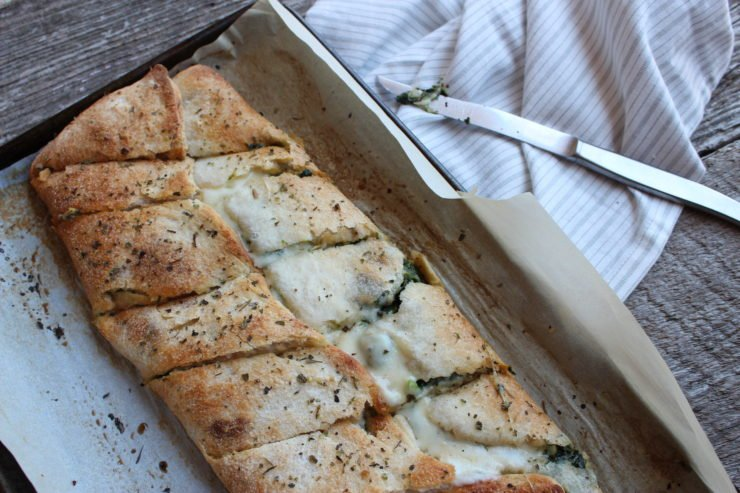 A parchment paper - lined baking sheet with the Spinach and Cheese Calzone sits in the center of a wood backdrop with a silver knife beside the pan on a white and gray striped towel.