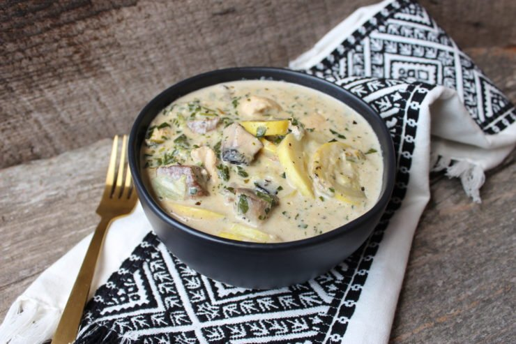 A black bowl with Low Carb Chicken Alfredo inside with a gold fork to the left of the bowl and a white and black aztec towel under the bowl. It all sits on a wood backdrop.
