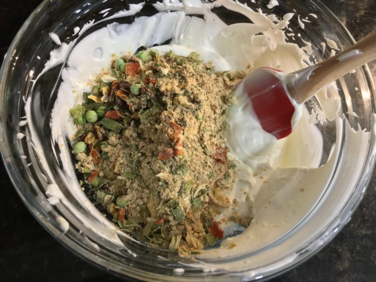 A clear, glass mixing bowl with mixed mayo, cream cheese, plain yogurt and Knorr Vegetable Soup Mix along with garlic salt inside