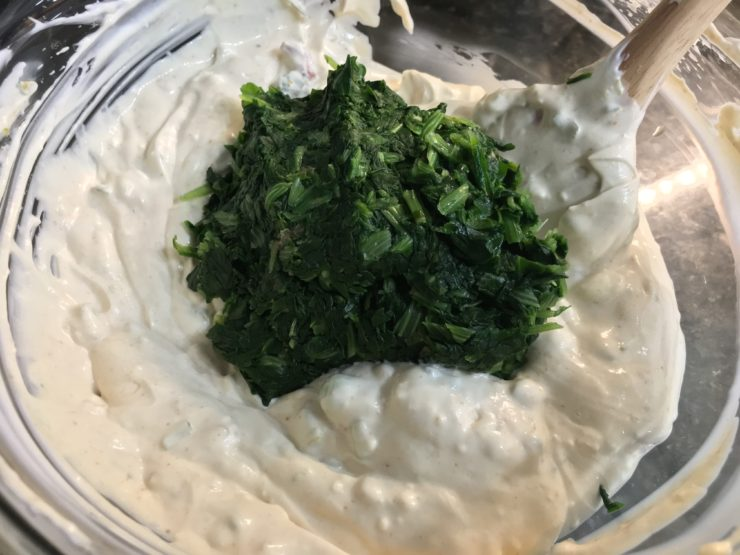 A clear, glass mixing bowl with mayo, cream cheese, plain yogurt, garlic salt, and Knorr Vegetable Soup mix all stirred up inside with frozen, thawed spinach in the bowl.