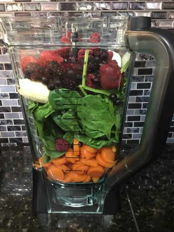 A large Ninja blender with sliced carrots, spinach, bananas, and a frozen berry fruit blend.
