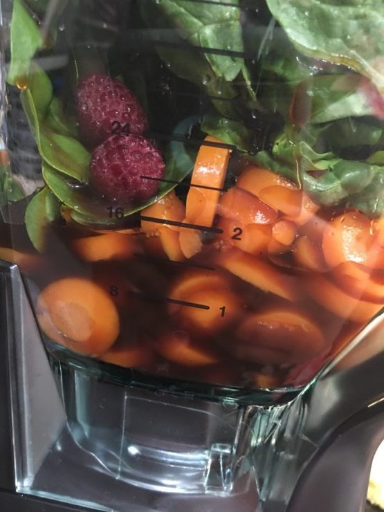A large Ninja blender with sliced carrots, spinach, bananas, a frozen berry fruit blend and prune juice.