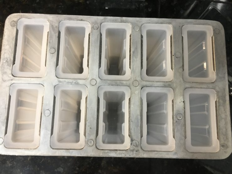 A large, popsicle mold with ten slots.