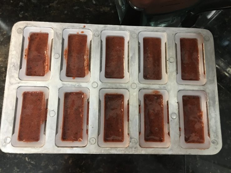 A large popsicle mold with ten slots and No Sugar Added Popsicle mix inside the mold. The mold has been cleaned.