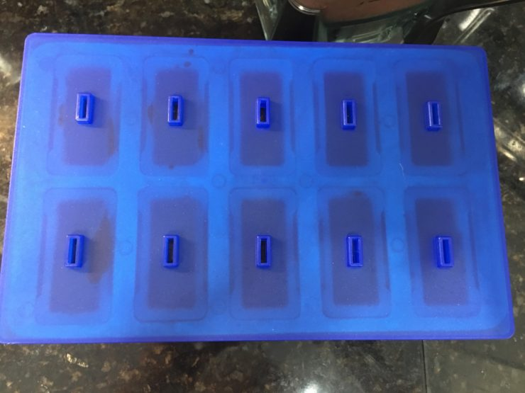 A large popsicle mold with popsicle mix inside and a blue lid on top of the mold.