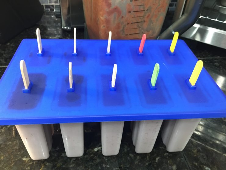 A large popsicle mold with popsicle mix inside with a blue lid on top of the mold and popsicle sticks poking up out of the top of the lid.