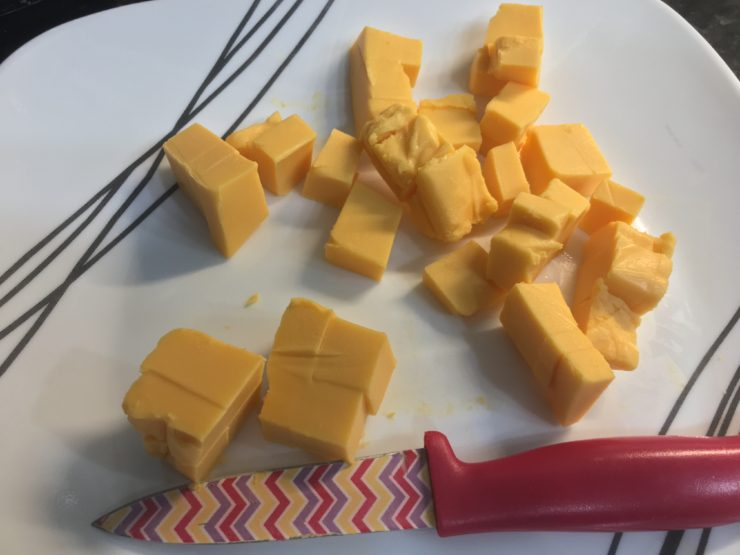 A white plate with black stripes and cubed Velveeta cheese on the plate, along with a multicolored paring knife.