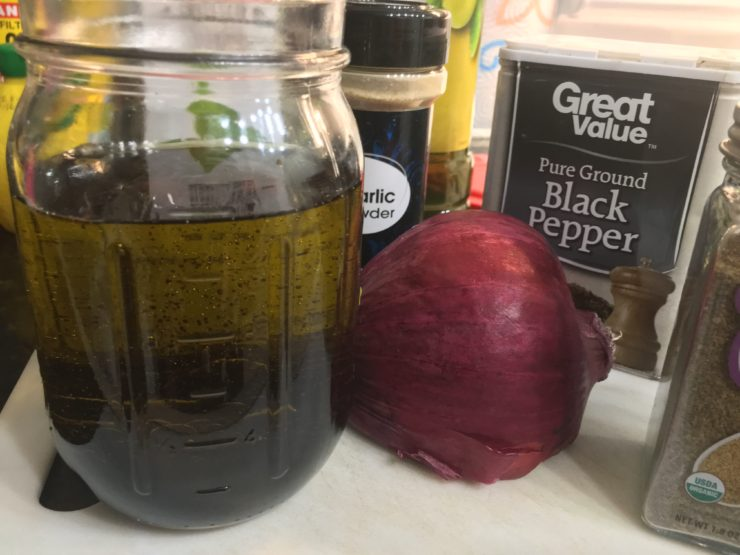 A Ball Mason Jar with olive oil and balsamic vinegar in it sitting on a white cutting board with a container of garlic powder, ground black pepper, celery seed, and half of a red onion.