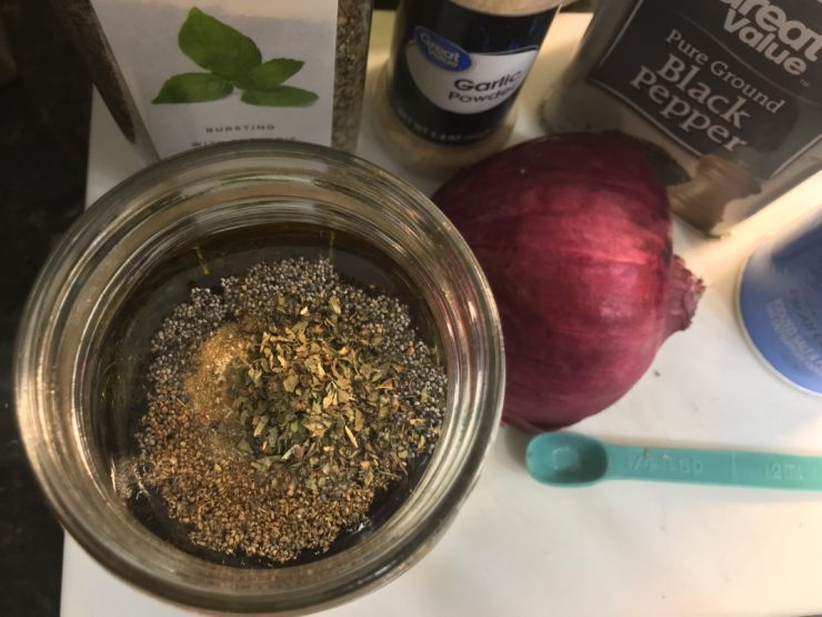 A Ball Mason Jar on a white cutting board with olive oil, balsamic vinegar, pepper, basil, onion powder, celery seed, poppy seeds, and salt inside. Half of a red onion is sitting beside the jar along with a measuring spoon and a container of basil, garlic powder, salt, and ground black pepper.