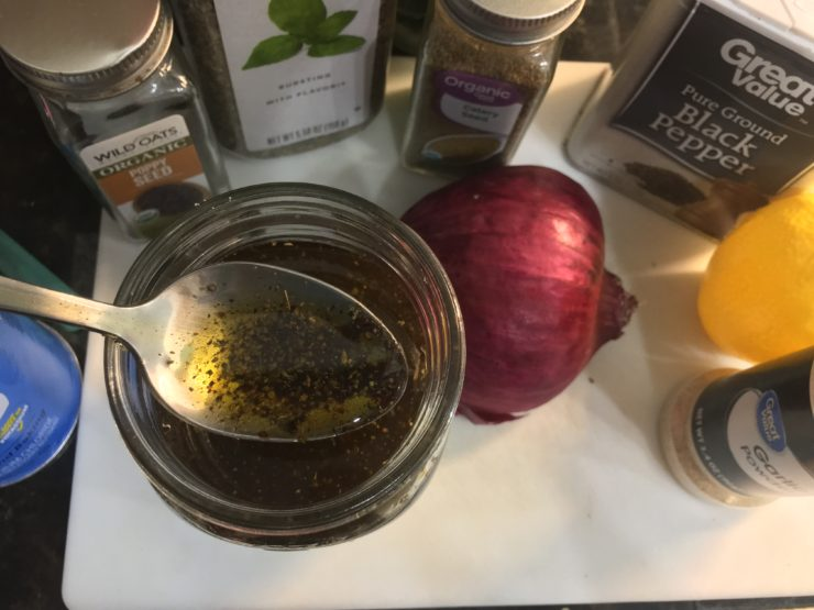 A Ball Mason Jar on a white cutting board with olive oil, balsamic vinegar, pepper, basil, onion powder, celery seed, poppy seeds, and salt inside. Half of a red onion is sitting beside the jar along with a measuring spoon and a container of basil, garlic powder, salt, and ground black pepper. A silver spoon is dipped into and out of the mason jar and a yellow bottle of lemon juice is also on the cutting board.