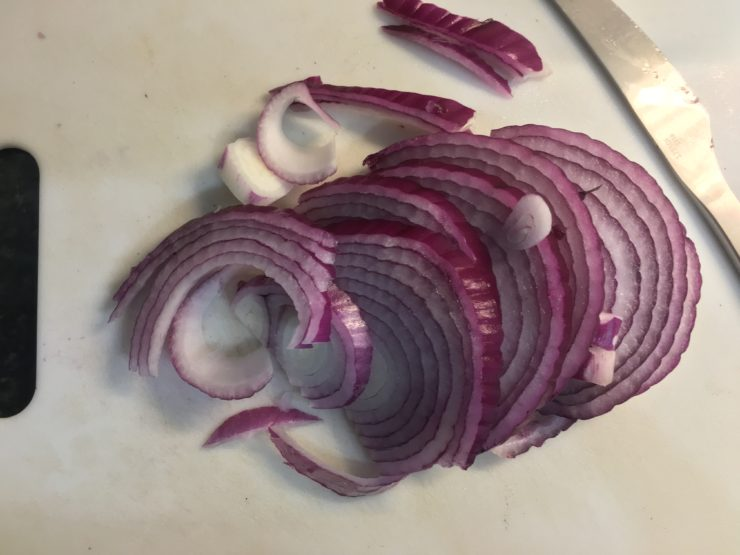 A white cutting board with half of a sliced purple onion on the board and a silver knife in the upper right corner.