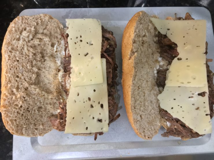 A silver baking sheet with two whole wheat hoagie buns that have mayo and shredded roast and swiss cheese on them, with the sandwiches open.
