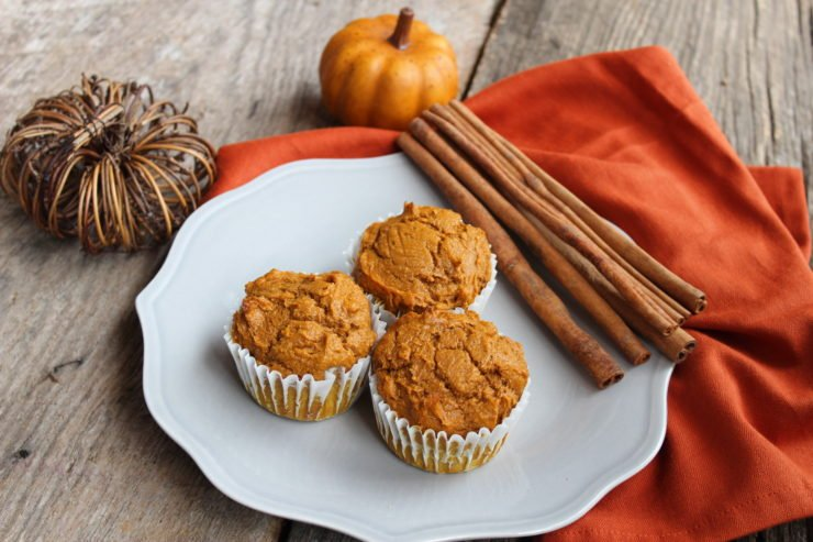 Three pumpkin muffins sitting on a gray plate with two artificial pumpkins in the back ground, an orange towel under the plate, and some cinnamon sticks place to the top right of the plate. Everything is sitting on a board backdrop.