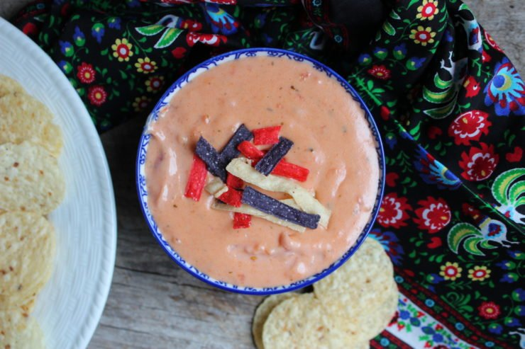 Tex Mex Queso Blanco Dip in a blue and white floral bowl with a white plate of white corn tortilla chips to the right and a multi colored floral towel wrapped around the bowl of cheese dip. Everything is sitting on a board back drop.