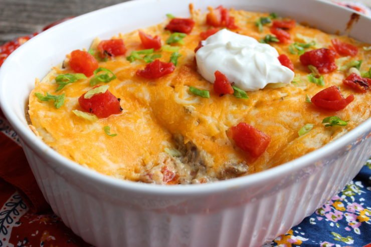 A white casserole dish with Easy Beef Enchilada Casserole in it. The casserole is topped with melted american cheese, diced tomatoes, sliced green onion, and a dollop of plain, nonfat Greek yogurt on top. An orange and blue floral towel is under the casserole dish and everything is sitting on a wood back drop. A square has been cut out of the bottom right hand side of the casserole.