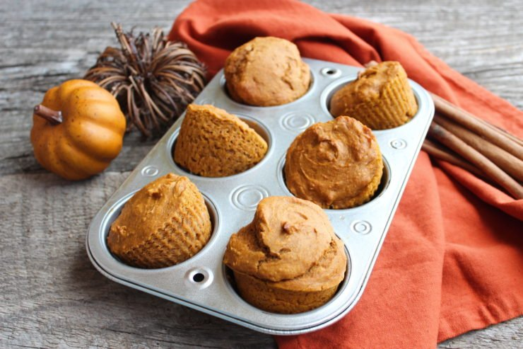 A silver muffin tin with six Three Ingredient Pumpkin Muffins in the tin, along with an two artificial pumpkins to the left of the muffin tin, an orange towel under the muffin tin, and cinnamon sticks to the right of the muffin tin. Everything is sitting on a wood backdrop.