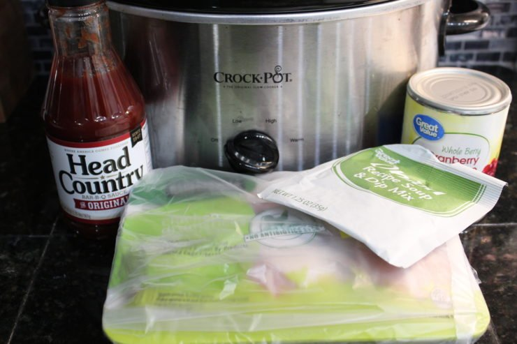A bottle of Head Country BBQ sauce, a package of organic chicken drumsticks, a packet of onion soup mix, a can of whole berry cranberry sauce, and a silver crock pot slow cooker sit on a black granite counter top with a blue and black kitchen back splash behind.