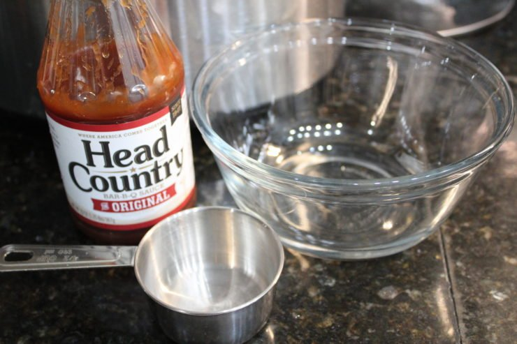 A small, clear, glass empty bowl with a silver measuring cup in front of the bowl and to the left, and a bottle of Head Country Original Bar-B-Q sauce to the left of the bowl. A silver Crock Pot slow cooker is in the background and everything is sitting on a black granite counter top.