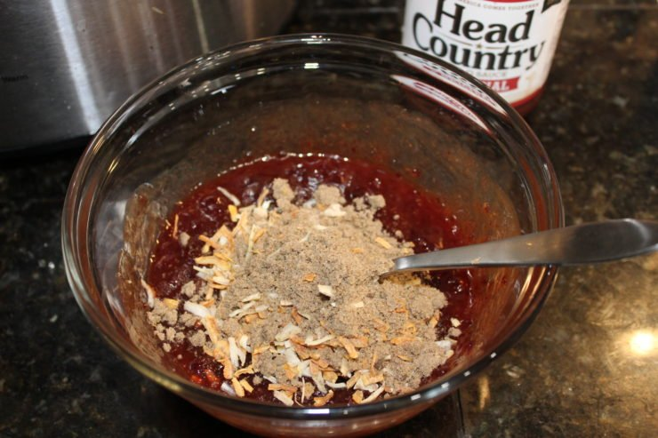 A small glass mixing bowl with Head Country Original Bar-B-Q sauce in the bowl stirred with whole berry cranberry sauce and a packet of onion soup mix that has been added in but not mixed together with the other ingredients. A silver spoon is inside the bowl, the bottle of Head Country Bar-B-Q is behind the bowl to the right and a silver Crock Pot slow cooker is behind the mixing bowl to the left.
