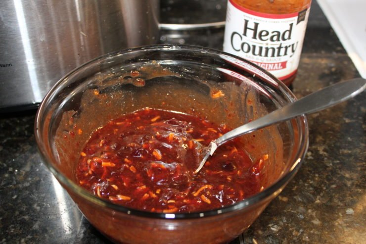 A small, glass mixing bowl with Head Country Original Bar-B-Sauce, whole berry cranberry sauce, and onion soup mix all stirred together with a silver spoon. Everything is sitting on a black granite counter top and a silver Crock Pot slow cooker is in the background to the left of the mixing bowl and a bottle of Head Country Bar-B-Q is to the right and behind the mixing bowl.