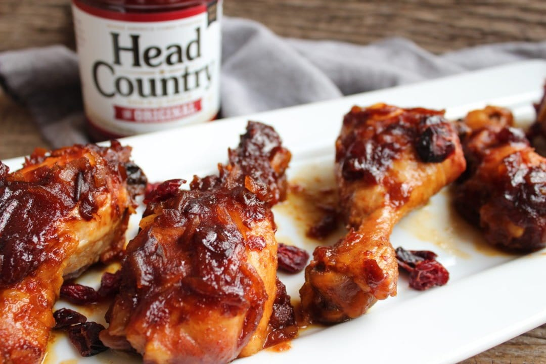 A white, rectangle platter of crockpot bbq chicken drumsticks with a bottle of bbq sauce in the background. Everything is sitting on a blue towel and is on a wooden back drop.