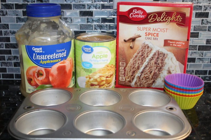 A container of Unsweetened Applesauce, A can of Apple Pie filling, a box of Spice Cake Mix, silicone muffin liners, and a half dozen silver muffin pan all on a black granite counter top with a blue and black kitchen black splash behind it.