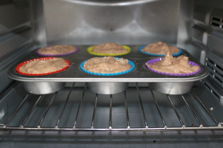 A silver, half dozen muffin pan lined with red, purple, blue, and green silicone muffin liners that are filled with Three Ingredient Apple Spice Muffins. The muffin pan has been placed in the oven and the oven door is open.