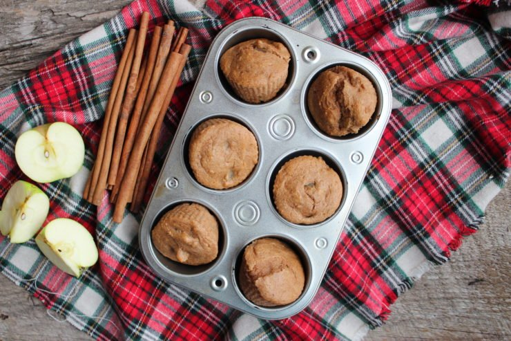 A red plaid cloth is on a wood back drop with a half dozen, silver muffin tin on the cloth, filled with Three Ingredient Apple Spice Muffins. A bundle of cinnamon sticks is placed to the left of the muffin tin and a green apple cut into three pieces is also on the left of the muffin tin under the cinnamon sticks.