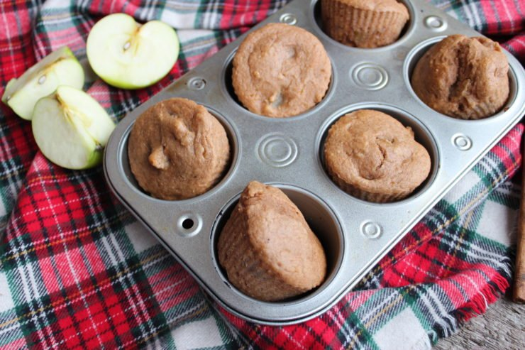 A red plaid cloth is on a wood back drop with a half dozen, silver muffin tin on the cloth, filled with Three Ingredient Apple Spice Muffins. A green apple cut into three pieces is on the left of the muffin tin under the cinnamon sticks.