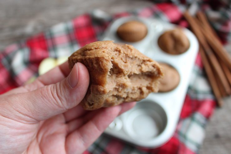 A hand holding a Three Ingredient Apple Spice Muffin that has a bite taken out of it in the foreground with a silver, half dozen muffin tin filled with Apple Spice Muffins in the background. The muffin tin is on a red plaid cloth with a bundle of cinnamon sticks to the upper right corner of the muffin tin. Everything is placed on a wood backdrop.