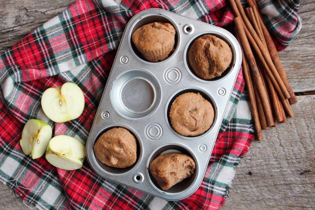 A red plaid cloth is on a wood back drop with a half dozen, silver muffin tin on the cloth, filled with Three Ingredient Apple Spice Muffins. A bundle of cinnamon sticks is placed to the left of the muffin tin and a green apple cut into three pieces is also on the left of the muffin tin under the cinnamon sticks. One muffin is missing from the muffin tin and a bite has been taken out of the front right muffin.