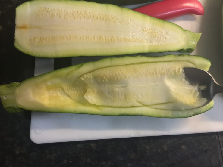A white cutting board with one halved zucchini on the board and a spoon scooping out the inside of one of the zucchini halves.
