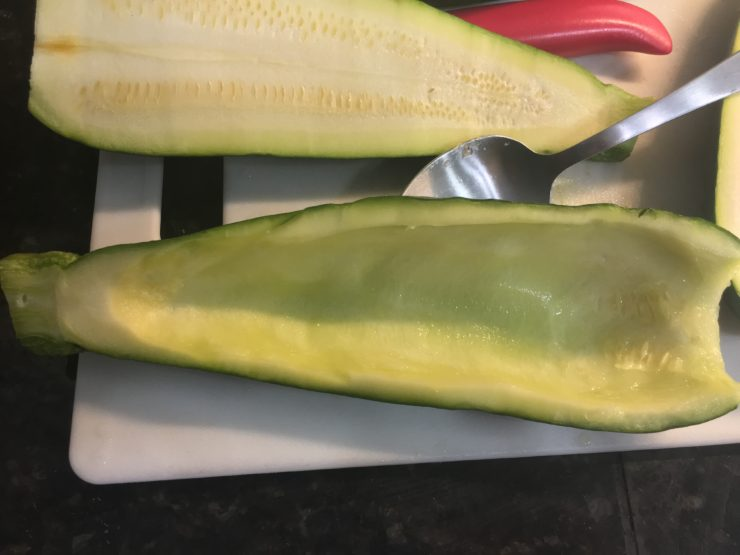 A white cutting board with a halved zucchini on the board and one half of the zucchini scooped out with a spoon.