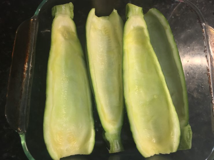 A casserole dish with three scooped out zucchini halves in the dish.
